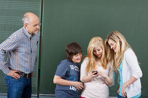 Angry teacher looking at students using mobilephone