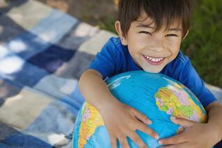 Close-up portrait of a cute young boy holding globe at the park.jpeg
