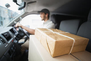 Delivery driver driving van with parcels on seat outside the warehouse-1