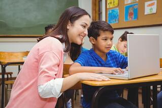 Happy teacher using laptop with student at the elementary school.jpeg