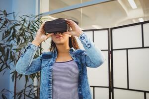 Low angle view of young female executive enjoying virtual reality headset at creative office.jpeg