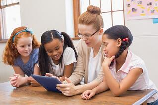 Teacher and pupils looking at tablet computer at the elementary school.jpeg